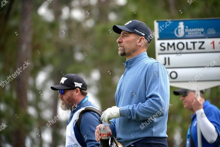 John Smoltz, center, walks on the second fairway after teeing off during the final round of the Tournament of Champions LPGA golf tournament, in Lake Buena Vista, Fla