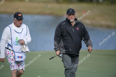Comedian Daniel Lawrence Whitney, right, known as Larry the Cable Guy, talks with his caddie after making a putt on the 17th green during the final round of the Tournament of Champions LPGA golf tournament, in Lake Buena Vista, Fla