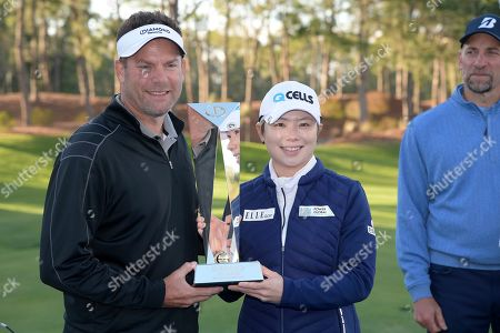 Michael Flaskey, CEO of Diamond Resorts International, left, poses with Eun-Hee Ji, of South Korea, after the final round of the Tournament of Champions LPGA golf tournament, in Lake Buena Vista, Fla. Eun-Hee Ji won the tournament and John Smoltz, right, was the top celebrity finisher