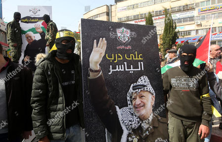Palestinian masked men hold photo of late Palestinian leader Yasser Arafat as Palestinian demonstrators gather to show support for Palestinian President Mahmoud Abbas in the west bank city of Nablus, 25 February 2019.