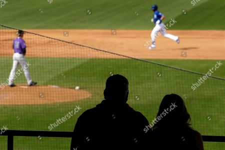 Fans in the stands and Colorado Rockies pitcher Sam Howard, left, watch as Kansas City Royals' Bubba Starling rounds the bases after hitting a solo home run during the fifth inning of a spring training baseball game, in Surprise, Ariz