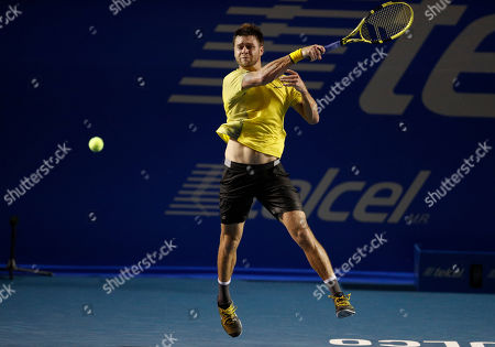 Ryan Harrison of the U.S. returns a ball in his match against Stan Wawrinka of Switzerland, during round one play at the Mexican Tennis Open in Acapulco, Mexico