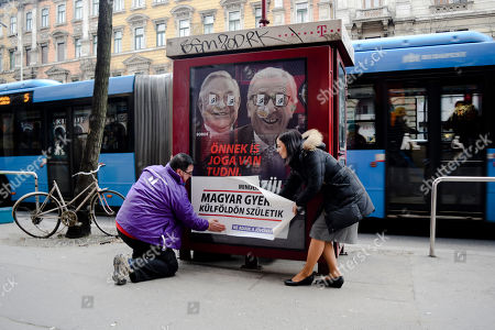"""Katalin Cseh, left, of the Momentum opposition party helps to place a sticker saying """"Every sixth Hungarian child is born abroad. Let's not hand over our future,"""" over a poster of the Hungarian government targeting EU Commission President Jean-Claude Juncker and Hungarian-American financier George Soros in Budapest, Hungary, . The poster reads """"You, too, have a right to know what Brussels is preparing to do."""" The Momentum party's """"Reality Campaign"""" is in response to government ads claiming EU leaders, backed by Soros, are organizing mass migration into Europe"""
