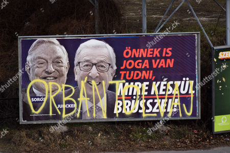 """A billboard from a campaign of the Hungarian government showing EU Commission President Jean-Claude Juncker and Hungarian-American financier George Soros with the caption """"You, too, have a right to know what Brussels is preparing to do."""" is displayed at a street in Budapest, Hungary, . The Hungarian government claims that EU leaders like Juncker, backed by Soros, want to bring mass migration into Europe. The billboard has been sprayed with graffiti saying """"Orban thief,"""" in reference to Hungarian Prime Minister Viktor Orban"""