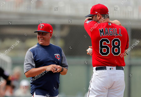 Minnesota Twins pitching coach Wes Johnson laughs as he walks to the mound to talk to pitcher Matt Magill (68) during their spring training baseball game in Fort Myers, Fla
