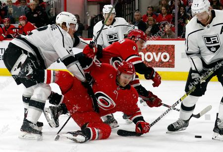 Carolina Hurricanes' Lucas Wallmark (71), of Sweden, and Saku Maenalanen (8), of Finland, battle Los Angeles Kings' Paul LaDue (2), Tyler Toffoli (73) and Jeff Carter (77) during the second period of an NHL hockey game in Raleigh, N.C