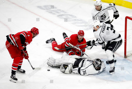 Stock Photo of Carolina Hurricanes' Saku Maenalanen (8) of Finland, and Warren Foegele (13) try to score against Los Angeles Kings' Jack Campbell (36), Dion Phaneuf (3) and Matt Roy (81) during the third period of an NHL hockey game in Raleigh, N.C