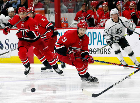 Carolina Hurricanes' Nino Niederreiter (21) of Switzerland, and Sebastian Aho (20), of Finland, and Los Angeles Kings' Tyler Toffoli (73) eye the puck during the second period of an NHL hockey game in Raleigh, N.C