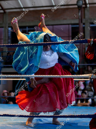 """Cholita wrestler Natalia la Pepita, 19, lifts her trainer Reyna Torrez, 29, as they compete in the ring in El Alto, Bolivia, . """"You need a lot of bravery, strength and training to make a good fight. We fall and we hurt, but that doesn't matter because the public has fun,"""" said fighter in training Natalia Pepita, whose real name is Noelia Gonzalez"""