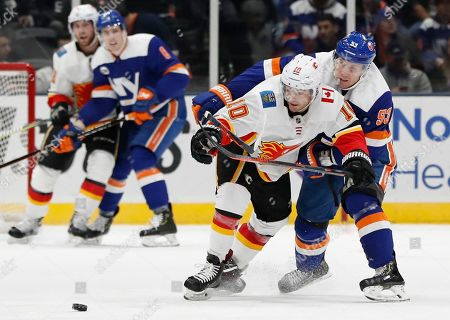 New York Islanders center Casey Cizikas (53) gets his stick around Calgary Flames center Derek Ryan (10) keeping Ryan away from the puck in the second period of an NHL hockey game, in Uniondale