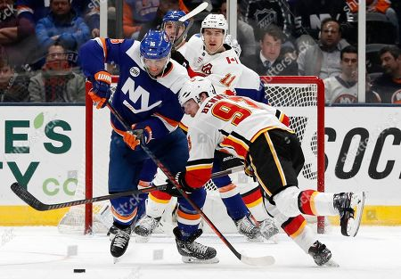 New York Islanders left wing Andrew Ladd (16) blocks Calgary Flames center Sam Bennett (93) from the puck in the second period of an NHL hockey game, in Uniondale