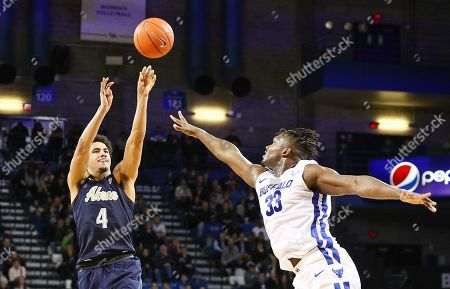 Stock Photo of Akron Zips guard Tyler Cheese (4) shoots for 3 of his team high 20 points over Buffalo Bulls forward Nick Perkins (33) during the second half of play in the NCAA Basketball game between the Akron Zips and Buffalo Bulls at Alumni Arena in Amherst, N.Y. (Nicholas T