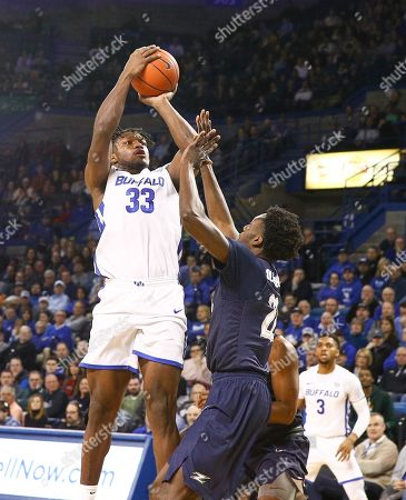 Buffalo Bulls forward Nick Perkins (33) shoots for two of his game high 25 points over Akron Zips forward Emmanuel Olojakpoke (22) during the first half of play in the NCAA Basketball game between the Akron Zips and Buffalo Bulls at Alumni Arena in Amherst, N.Y. (Nicholas T