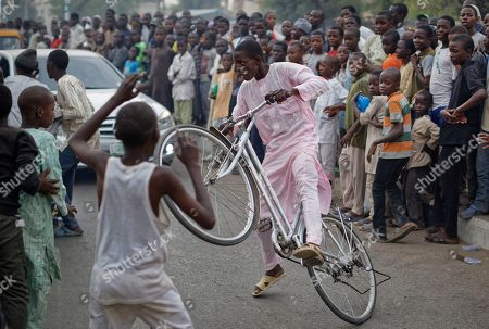 """A boy pulls a wheelie on his bicycle as supporters of Nigeria's President Muhammadu Buhari and young children enjoying the festivities celebrate his electoral win as they gather to dance and cheer passing traffic next to a sound system on the street in Kano, northern Nigeria . Buhari on Wednesday defended his sweeping win of a second term as free and fair and appealed to a """"common love of country"""" as his top challenger vowed to go to court with allegations of fraud"""