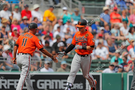 Baltimore Orioles Sisco (15) is greeted by third base coach Jose David Flores (11) on his 2-run homer in the fourth inning of their spring training baseball game against the Boston Red Sox in Fort Myers, Fla