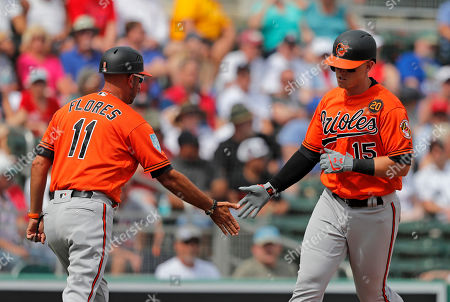 Baltimore Orioles Chance Sisco (15) is greeted by third base coach Jose David Flores (11) on his 2-run homer in the fourth inning of their spring training baseball game against the Boston Red Sox in Fort Myers, Fla