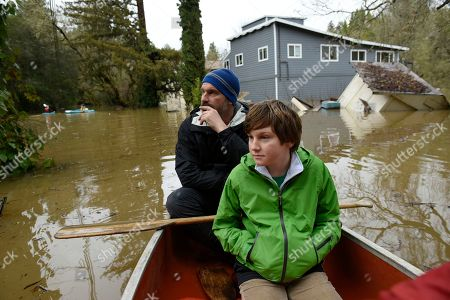 Martin McCarthy and his son Thomas McCarthy, 10, look at homes flooded by the Russian River from their canoe as they paddle through a neighborhood in Forestville, Calif., on . The still rising Russian River was engorged by days of rain from western U.S. storms