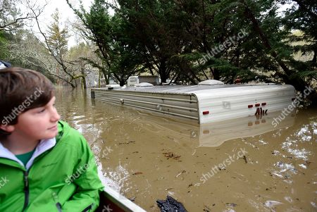 Thomas McCarthy, 10, looks from his canoe passing an RV submerged in the flood waters of the Russian River in Forestville, Calif., on . The still rising Russian River was engorged by days of rain from western U.S. storms