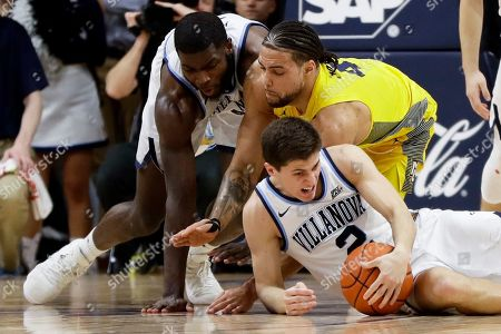 Collin Gillespie, Eric Paschall, Theo John. Villanova's Collin Gillespie, front, Marquette's Theo John and Villanova's Eric Paschall battle for a loose ball during the second half of an NCAA college basketball game, in Villanova, Pa. Villanova won 67-61
