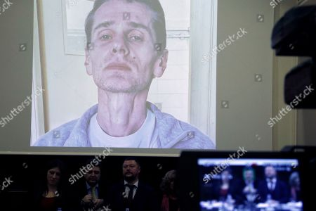 A photograph of the Russian cybercrime suspect Russian man Alexander Vinnik is on display on a screen during a press conference by his lawyers in Athens, . Zoe Konstantopoulou, the lawyer for Vinnik, suspected of bitcoin fraud and wanted by three countries says his health is deteriorating due to a hunger strike and criticized the Greek courts for holding him in custody for more than the maximum 18 months allowed