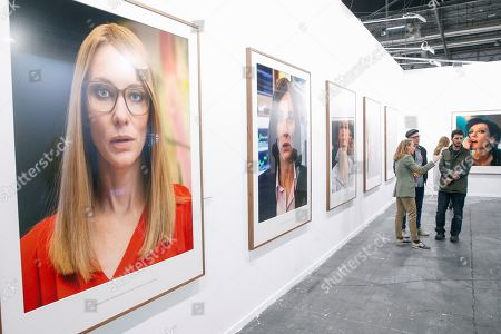 Stock Photo of Visitors stand in front of the artwork 'Manifest' (2017) by German artist Julian Rosefeldt on display during the International Contemporary Art Fair ARCO at the IFEMA Exhibition Centre in Madrid, Spain, 28 February 2019. ARCOMadrid 2019 will run from 27 February to 03 March, with Peru as guest country.