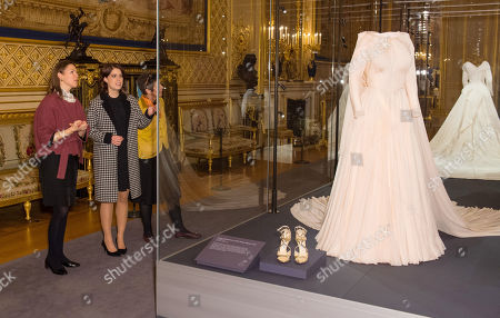 Stock Picture of Princess Eugenie talks with Senior Curator Caroline De Guitaut as she views her evening wedding gown, part of a display of her wedding outfits in a new exhibition at Windsor Castle.