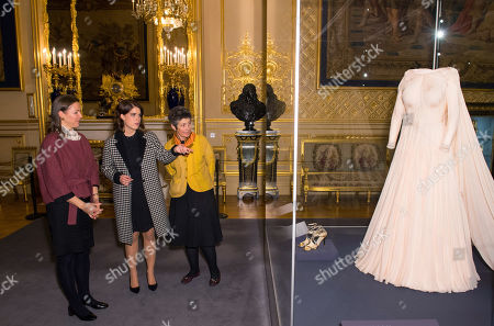 Princess Eugenie talks with Senior Curator Caroline De Guitaut and Head of Exhibitions Theresa-mary Morton as she views her evening wedding gown, part of a display of her wedding outfits in a new exhibition at Windsor Castle.