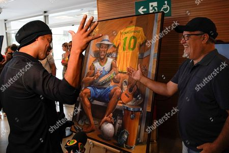 Brazil's former soccer star Ronaldinho Gaucho, left, shakes hands with Emerson Carvalho de Souza, a Brazilian artist known as Camelao, who presented his paintings during the inauguration of exposition about Ronaldinho at Maracana stadium in Rio de Janeiro, Brazil, . Ronaldinho was twice named FIFA World Player of the Year