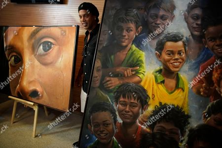 Brazil's former soccer star Ronaldinho Gaucho poses beside paintings of him by Brazilian artist Emerson Carvalho de Souza, known as Camelao, during the inauguration of an exposition about him at Maracana stadium in Rio de Janeiro, Brazil, . Ronaldinho was twice named FIFA World Player of the Year
