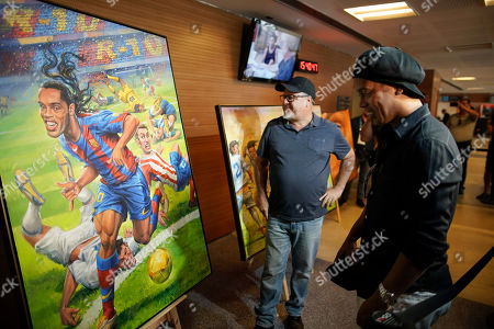 Brazil's former soccer star Ronaldinho Gaucho, right, and Emerson Carvalho de Souza, center, look at the paintings by Carvalho de Souza, during the inauguration of an exposition about Ronaldinho at Maracana stadium in Rio de Janeiro, Brazil, . Ronaldinho was twice named FIFA World Player of the Year