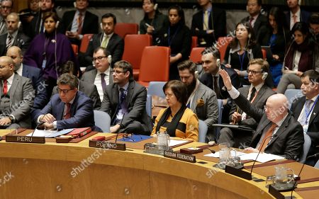 Russian ambassador to the United Nations Vasily Nebenzya, right, votes against a resolution concerning Venezuela during a Security Council meeting at U.N. headquarters