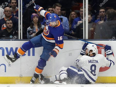 Andrw Ladd, Jake Muzzin. New York Islanders left wing Andrew Ladd (16) hits the boards after colliding with Toronto Maple Leafs defenseman Jake Muzzin (8) during the first period of an NHL hockey game, in Uniondale, N.Y