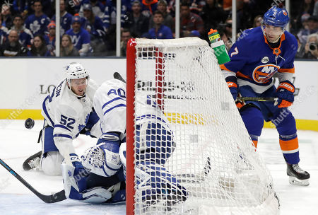 Stock Image of Martin Marincin, Garrett Sparks, Jordan Eberle. Toronto Maple Leafs defenseman Martin Marincin (52) tries to block a shot in front of goaltender Garret Sparks (40) with New York Islanders right wing Jordan Eberle (7) watching from behind the net during the second period of an NHL hockey game, in Uniondale, N.Y
