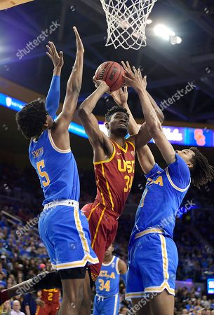 Victor Uyaelunmo, Moses Brown, Chris Smith. Southern California forward Victor Uyaelunmo, center, shoots as UCLA guard Chris Smith, left, and center Moses Brown defend during the first half of an NCAA college basketball game, in Los Angeles