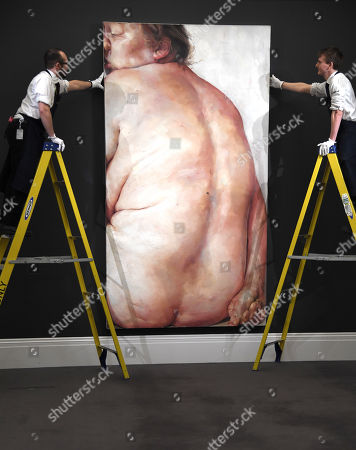 A Sotheby's  employee next to a painting by Jenny Saville, entitled Juncture
