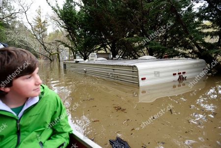 Stock Photo of Thomas McCarthy, 10, looks from his canoe passing an RV submerged in the flood waters of the Russian River in Forestville, Calif., on