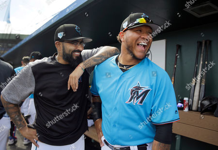 Miami Marlins' Sergio Romo, left, laughs with teammate Harold Ramirez before the start of an exhibition spring training baseball game against the Washington Nationals, in Jupiter, Fla