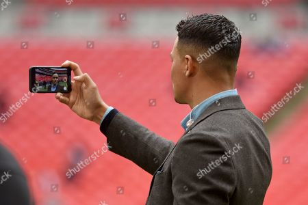 Jermaine Jenas recording himself for social media during the Premier League match between Tottenham Hotspur and Arsenal at Wembley Stadium, London
