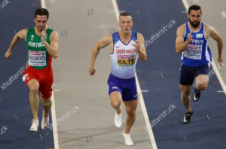Portugal's Carlos Nascimento, left, Britain's Richard Kilty, center, and Cyprus' Andreas Hadjitheoris, right, compete in a heat of the men's 60 meters race during the European Athletics Indoor Championships at the Emirates Arena in Glasgow, Scotland