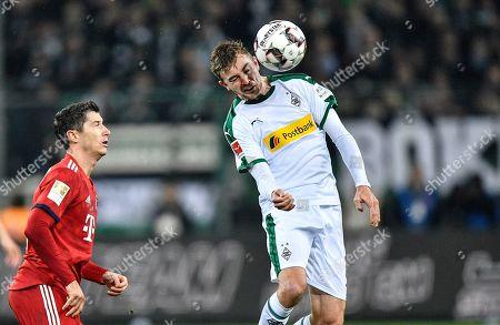 Bayern's Robert Lewandowski, left, and Moenchengladbach's Christoph Kramer challenge for the ball during the German Bundesliga soccer match between Borussia Moenchengladbach and FC Bayern Munich in Moenchengladbach, Germany