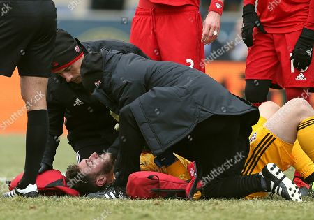 Toronto FC goalkeeper Alex Bono is looked after by medical personal after colliding with Philadelphia Union forward Marco Fabian (10) in the second half during an MLS soccer match in Chester, Pa., . Toronto defeated Philadelphia 3-1