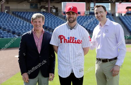 Bryce Harper, center, poses for a photo with Philadelphia Phillies managing partner John Middleton, and general manager Matthew Klentak, right, after being introduced as a Philadelphia Phillies player during a news conference at the Philadelphia Phillies spring training baseball facility, in Clearwater, Fla. Harper and the Phillies agreed to a $330 million, 13-year contract, the largest deal in baseball history