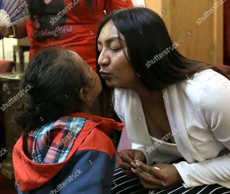 Salena Manni, the fiancee of Stephon Clark, who was shot and killed by Sacramento police in 2018, kisses the couple's youngest son, Cairo, 2, during a news conference to discuss the decision to not file charges against the two officers involved, during a news conference in Sacramento, Calif., . Sacramento County District Attorney Anne Marie Schubert announced that Officers Terrance Mercadal and Jared Robinet did not break any laws when they shot Clark after the 22-year-old vandalism suspect ran from them into his grandparents' backyard