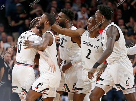 Cincinnati guard Logan Johnson, left, is mobbed by teammates after a steal during the second half of an NCAA college basketball game against Memphis, in Cincinnati. with Johnson are, from second fromleft, Trevor Moore, Eliel Nsoseme, Keith Williams (2), and Nysier Brooks