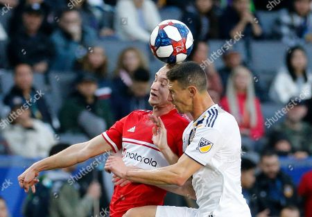 LA Galaxy defender Daniel Steres, right, and Chicago Fire midfielder Djordje Mihailovic battle for a head ball in the first half of an MLS soccer match in Carson, Calif