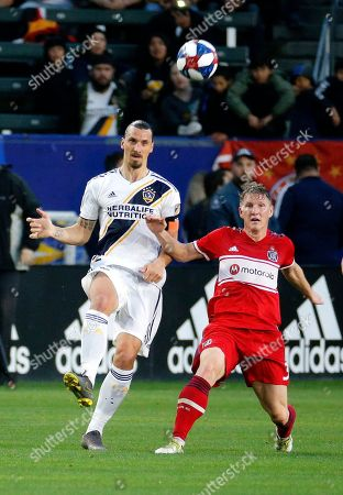 LA Galaxy forawrd Zlatan Ibrahimovic, left, of Sweden, kicks the ball away from Chicago Fire midfielder Bastian Schweinsteiger of Germany in the first half of an MLS soccer match in Carson, Calif