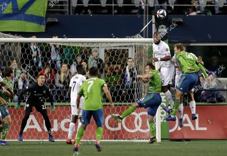 FC Cincinnati goalkeeper Przemyslaw Tyton, left, watches as defender Kendall Waston, second from upper right, heads the ball between Seattle Sounders defender Chad Marshall, right, and forward Jordan Morris, third from right, during the first half of an MLS soccer match, in Seattle