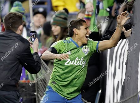 Seattle Sounders forward Raul Ruidiaz reaches out to greet fans in the supporters section after he scored a goal against FC Cincinnati during the second half of an MLS soccer match, in Seattle. The Sounders won 4-1