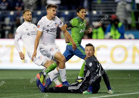 FC Cincinnati goalkeeper Przemyslaw Tyton, lower right, looks toward the goal after Seattle Sounders forward Raul Ruidiaz, right, scored a goal during the second half of an MLS soccer match, in Seattle. The Sounders won 4-1