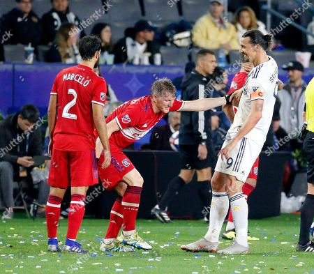 Chicago Fire midfielder Bastian Schweinsteiger (31) of Germany, is helped by LA Galaxy forawrd Zlatan Ibrahimovic (9) of Sweden, during an MLS soccer match between LA Galaxy and Chicago Fire in Carson, Calif., . The Galaxy won 2-1